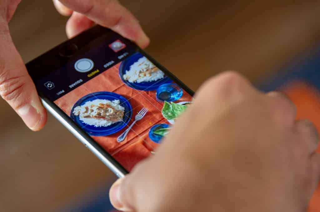 Como ganhar dinheiro no natal - Imagem de mãos segurando um smartphone para tirar fotos de um prato de comida